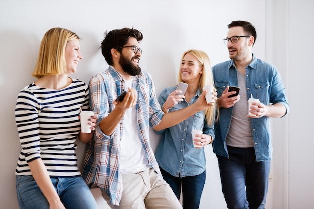 Groupe de joyeux jeunes gens modernes tenant des mobiles et riant en attendant ou en faisant une pause. obsession mobile moderne.