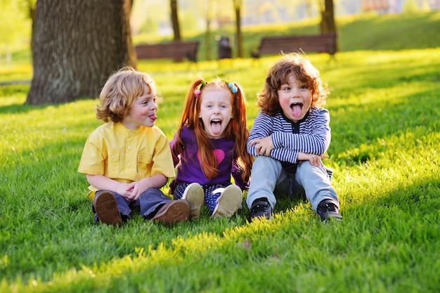 Groupe de joyeux petits enfants souriants assis dans un parc sur l'herbe sous un arbre.