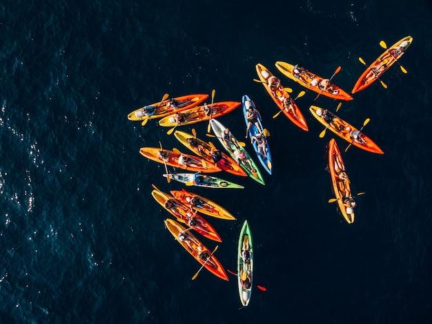Un groupe de kayakistes a rassemblé leurs kayaks dans un tas en groupe de mer nager en paires bannière de concept de kayaks