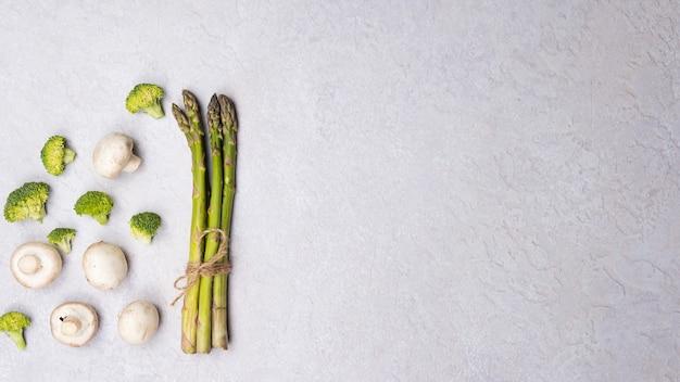 Groupe de légumes frais bio asperges vertes champignons brocoli sur fond gris