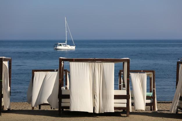Groupe de lits balinais sur les plages de la méditerranée avec catamaran de fond
