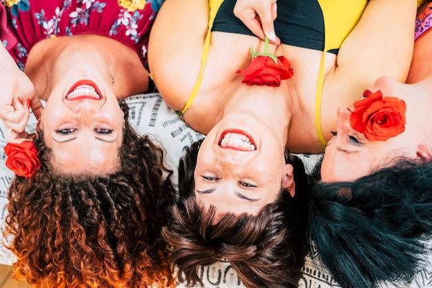 Groupe ludique de jeunes amies à la maison ensemble riant et souriant