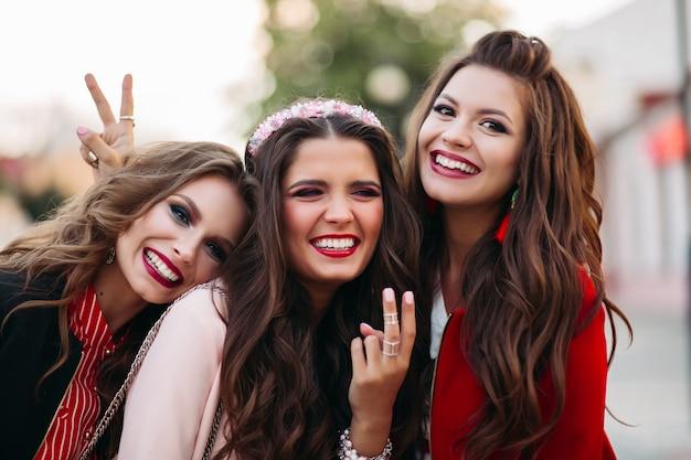 Groupe de magnifiques copines souriant et gesticulant