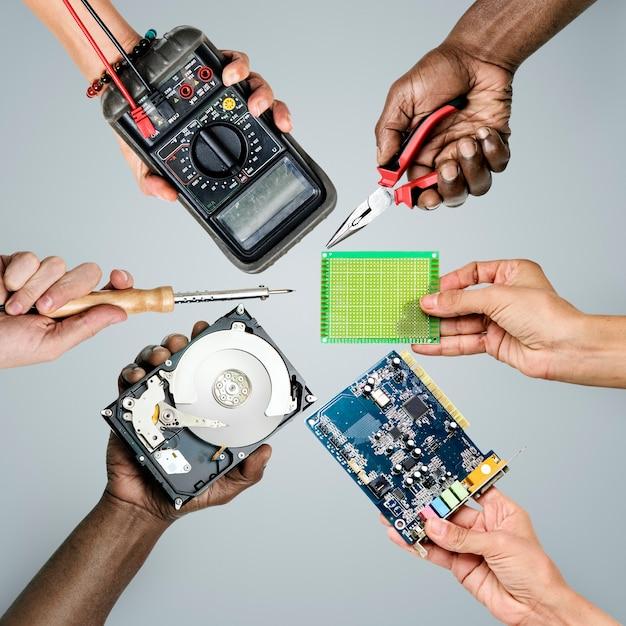 Groupe de mains tenant des pièces électroniques de l'ordinateur sur fond gris