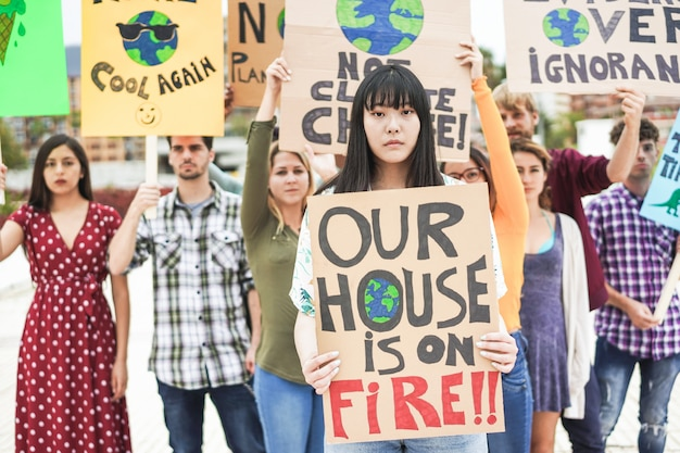 Groupe de manifestants sur la route, des jeunes de différentes cultures et races luttent pour le changement climatique