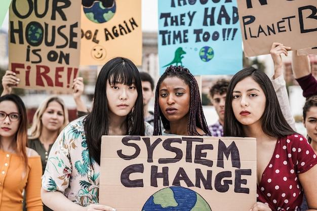 Groupe de manifestants sur la route, jeunes de différentes cultures et races se battent pour le changement climatique - l'accent est mis sur le visage d'une fille africaine