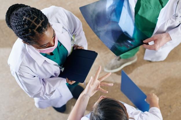 Groupe de médecins debout en cercle, discutant des symptômes et s'aidant mutuellement à établir un diagnostic
