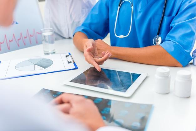 Un groupe de médecins discute de quelque chose sur une tablette.
