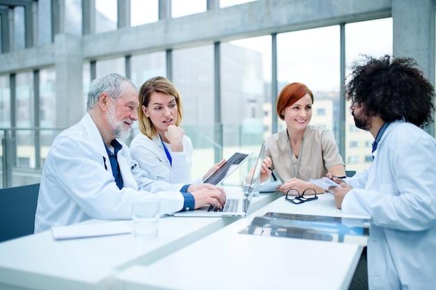 Un groupe de médecins avec un ordinateur portable en conférence, une équipe médicale discutant de problèmes.