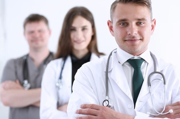 Groupe de médecins posant fièrement dans la rangée