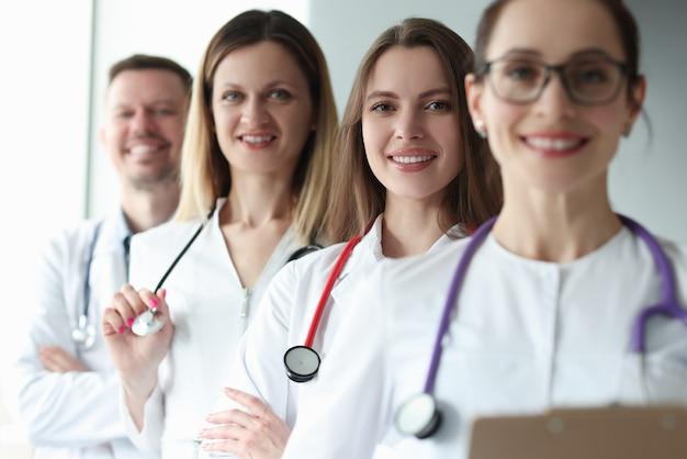 Groupe de médecins avec des stéthoscopes autour du cou debout dans une clinique