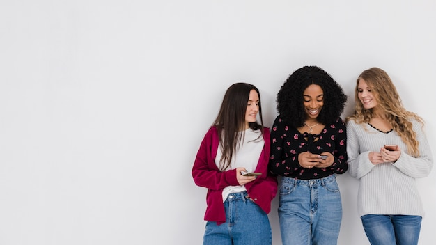 Groupe de meilleurs amis à la recherche sur un téléphone avec espace copie