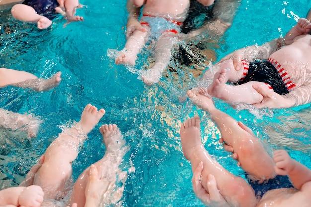Un groupe de mères avec leurs jeunes enfants dans un cours de natation pour enfants avec un entraîneur.