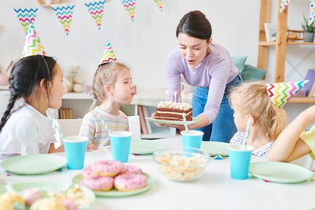 Groupe de mignonnes petites filles et jolie jeune femme soufflant des bougies sur le gâteau d'anniversaire lors de la célébration à la maison par table de fête