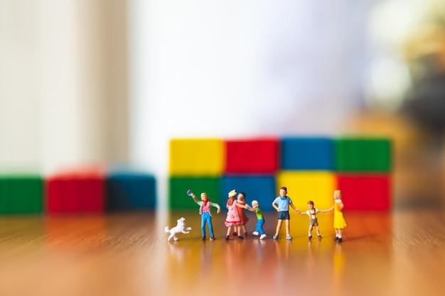 Groupe miniature d'enfants debout devant un fond de couleur en bois
