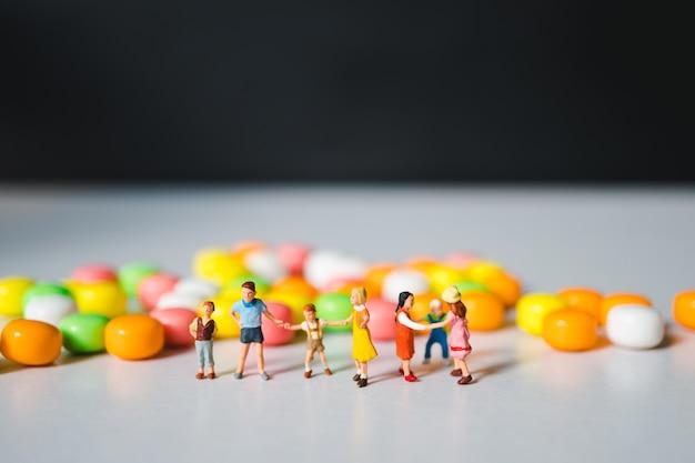 Groupe miniature d'enfants debout fond de bonbons colorés
