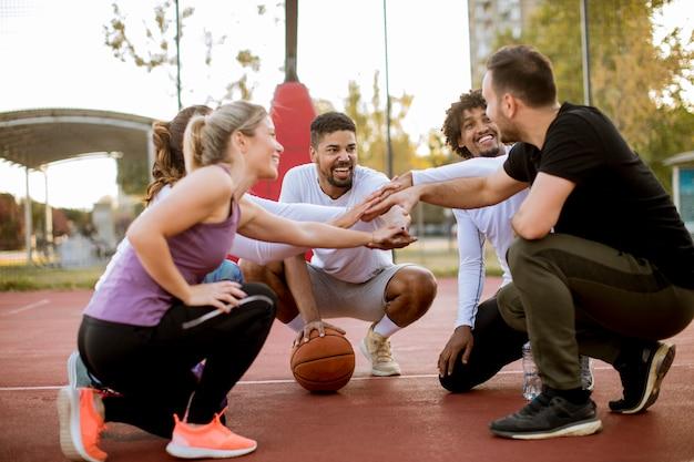 Groupe multi-ethnique de basketteurs reposant sur le court
