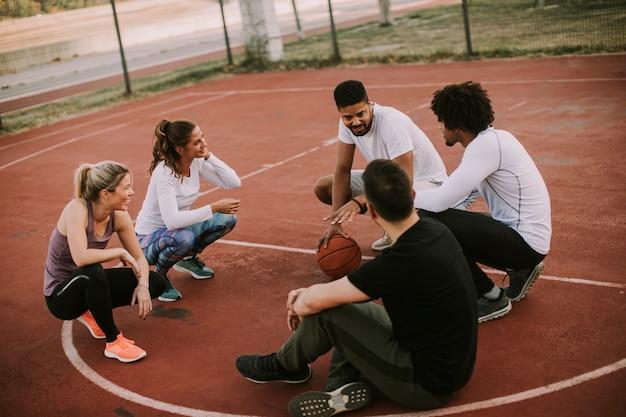 Groupe multi-ethnique de basketteurs se reposant sur le court