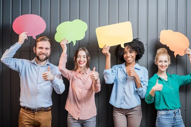 Groupe multi-ethnique de collègues debout avec des bulles de pensée colorées sur fond de mur gris