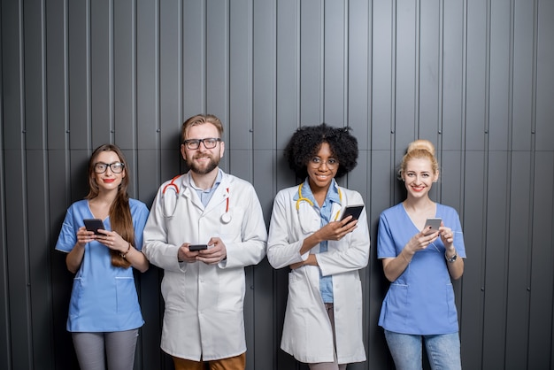 Groupe multi-ethnique de médecins debout avec des téléphones sur fond de mur gris