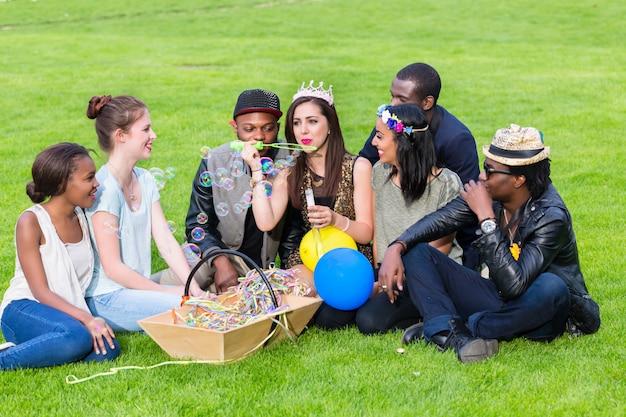 Groupe multiculturel, assis ensemble sur une pelouse
