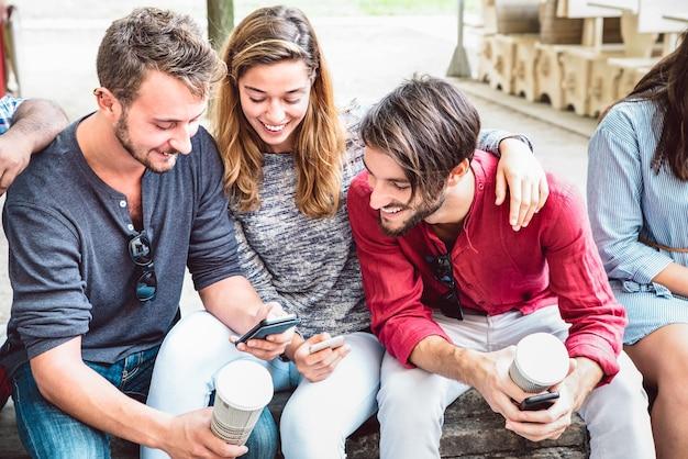 Groupe multiculturel de personnes mileniales utilisant un téléphone intelligent dans l'arrière-cour du collège de la ville
