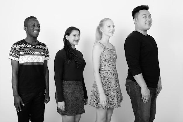 Groupe multiethnique d'amis ensemble comme concept de diversité contre un mur blanc en noir et blanc