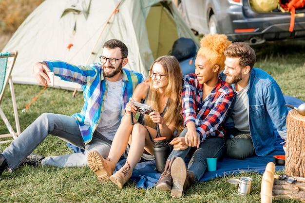 Groupe multiethnique d'amis habillés avec désinvolture s'amusant à faire une photo de selfie ensemble pendant les loisirs de plein air avec tente, voiture et équipement de randonnée près du lac