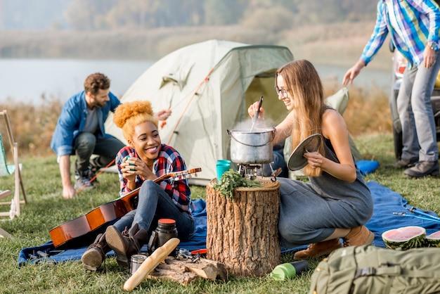 Groupe multiethnique d'amis habillés avec désinvolture en train de pique-niquer, de cuisiner une soupe avec un chaudron pendant les loisirs de plein air près du lac