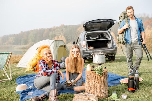 Groupe multiethnique d'amis habillés avec désinvolture en train de pique-niquer pendant les loisirs de plein air avec tente, voiture et équipement de randonnée près du lac