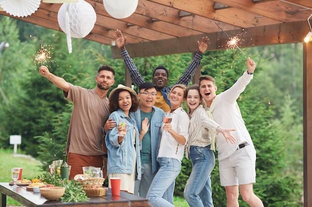 Groupe multiethnique d'amis heureux tenant des cierges magiques et profitant d'une fête d'été à l'extérieur