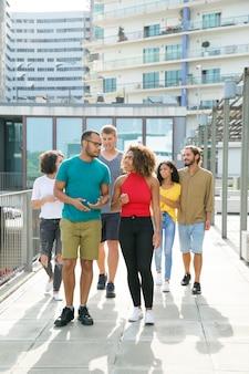 Groupe multiethnique d'amis marchant