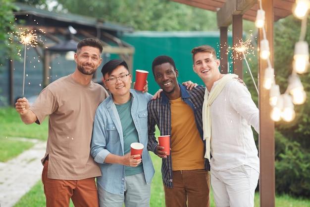 Groupe multiethnique d'amis masculins tenant des cierges tout en profitant de la fête en plein air
