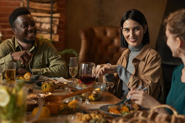 Groupe multiethnique d'amis souriant joyeusement tout en profitant d'un dîner dans un éclairage confortable