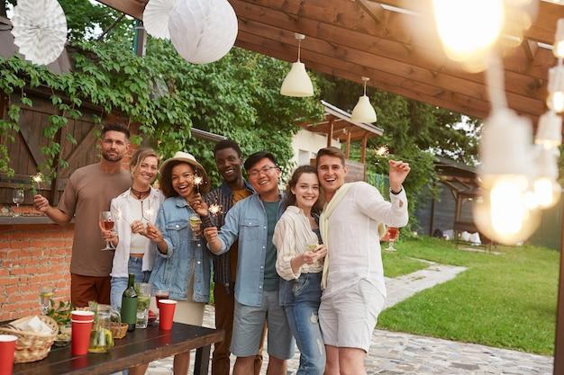 Groupe multiethnique d'amis tenant des cierges magiques tout en profitant d'une fête d'été en plein air