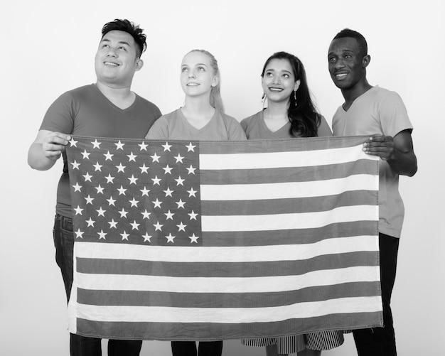 Groupe multiethnique d'amis tenant ensemble le drapeau américain symbolisant l'unité et la diversité contre un mur blanc en noir et blanc