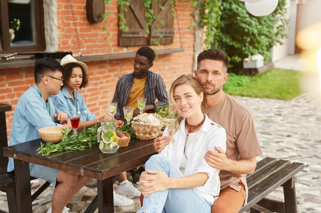 Groupe multiethnique de belles jeunes appréciant le dîner en plein air au soleil, se concentrer sur un couple souriant en premier plan