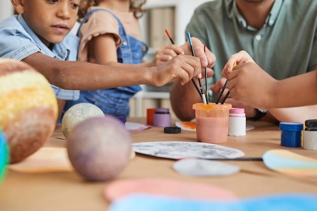 Groupe multiethnique d'enfants tenant des pinceaux et un modèle de planète de peinture tout en profitant d'une leçon d'art et d'artisanat à l'école ou au centre de développement