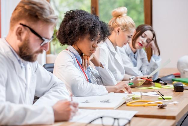 Groupe multiethnique d'étudiants en médecine en uniforme assis ensemble au bureau avec différents trucs médicaux en classe