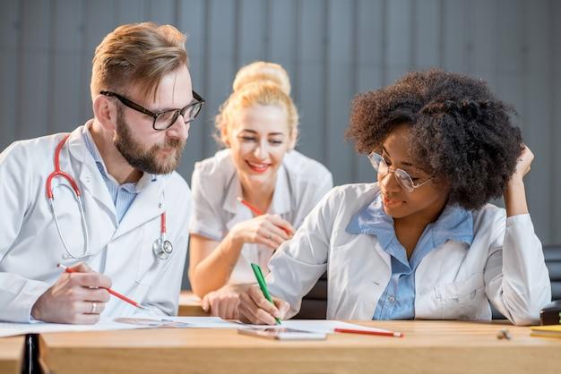 Groupe multiethnique d'étudiants en médecine en uniforme ayant une discussion assis ensemble dans la salle de classe moderne