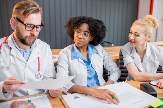 Groupe multiethnique d'étudiants en médecine en uniforme discutant assis ensemble au bureau avec différents trucs médicaux en classe