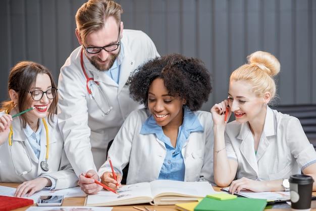 Groupe multiethnique d'étudiants en médecine en uniforme étudiant ensemble assis au bureau avec des livres dans la salle de classe moderne