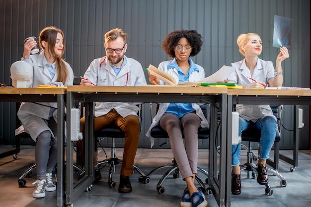 Groupe multiethnique d'étudiants en médecine en uniforme étudiant ensemble assis dans une rangée au bureau dans la salle de classe moderne