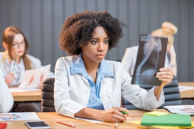 Groupe multiethnique d'étudiants en médecine en uniforme travaillant sur la recherche médicale assis au bureau avec radiographie et livres dans la salle de classe moderne
