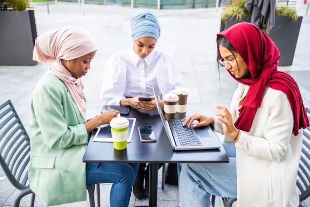 Groupe multiethnique de filles musulmanes portant des vêtements décontractés et des liens traditionnels avec le hijab à l'extérieur