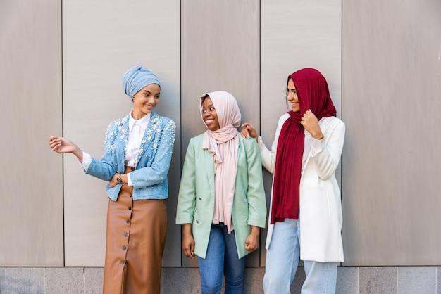 Groupe multiethnique de filles musulmanes portant des vêtements décontractés et des liens traditionnels avec le hijab