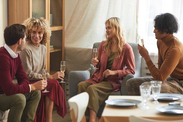 Groupe multiethnique de jeunes contemporains buvant du champagne et bavardant assis sur un canapé lors d'un dîner à l'intérieur