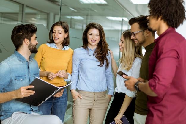 Groupe multiethnique de jeunes debout dans le bureau moderne et de brainstorming