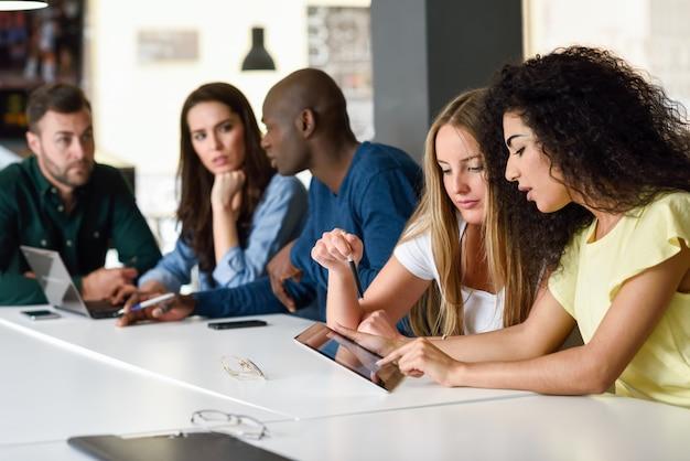 Groupe multiethnique de jeunes étudiant avec un ordinateur portable