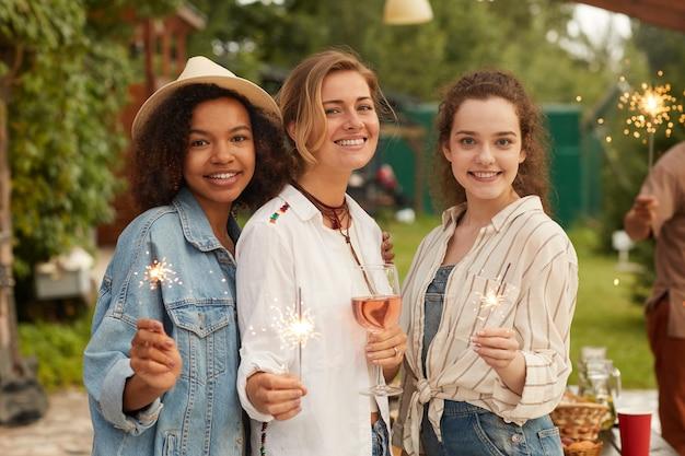 Groupe multiethnique de jeunes femmes tenant des cierges magiques souriant et profitant d'une fête d'été à la terrasse